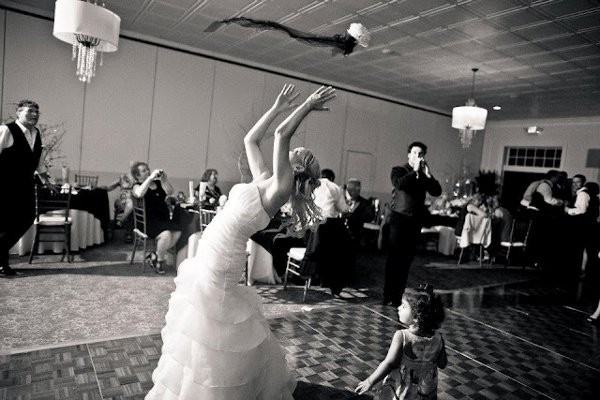 Photo of a bride tossing a bouquet of flowers