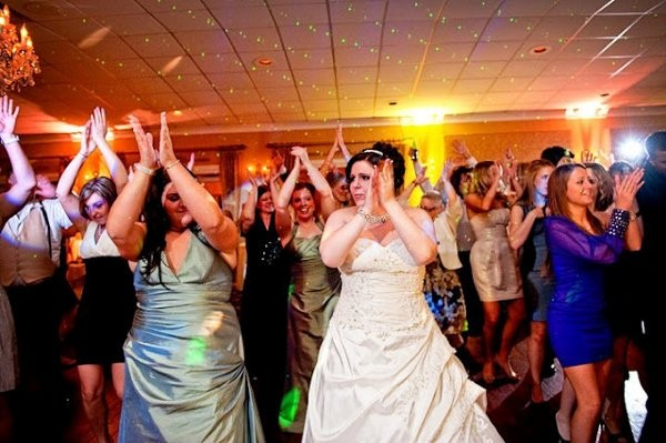 A bride and wedding guests dancing